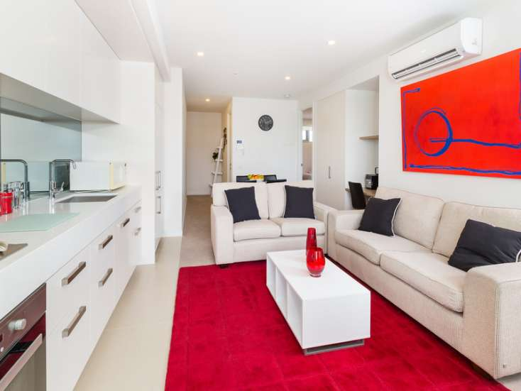 Open Plan living room and kitchen with flat screen TV and Australian art in luxury Brighton apartment - 101/317 New Street