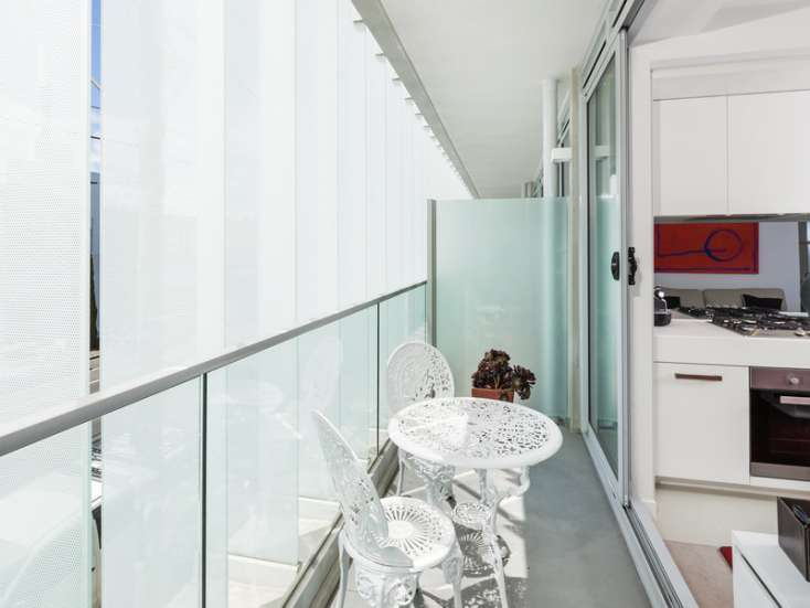 Outdoor balcony with entertaining area and wrought iron table and chairs in luxury Brighton apartment - 101/317 New Street