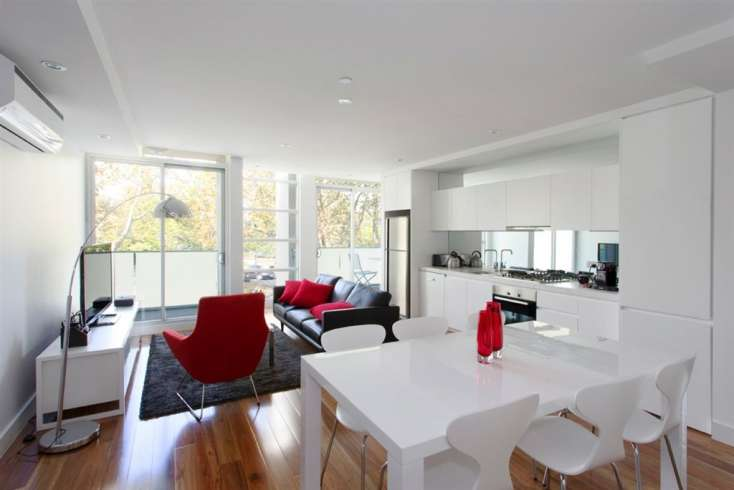 Black, red and white themed living and dining room area with timber floors in Superb apartment in Elwood Vic - 102/60-62 Broadway