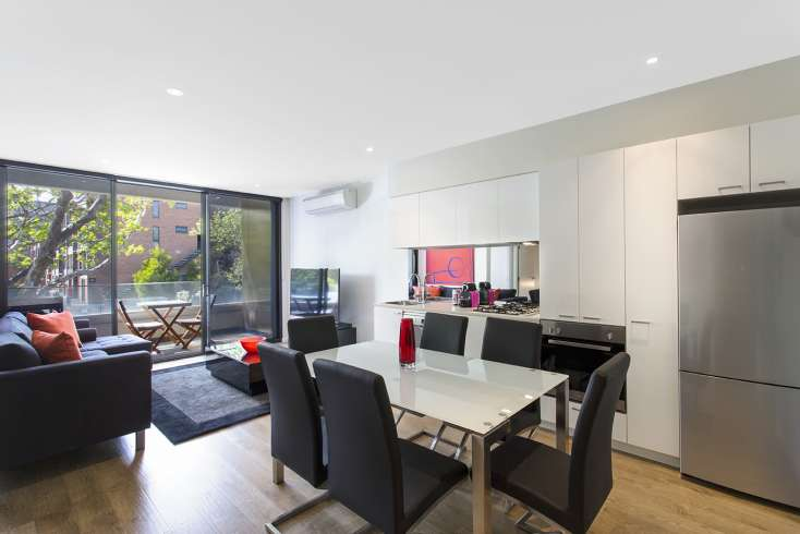 Generous open plan living, dining, kitchen leading on to outdoor balcony in  luxury executive apartment in Carlton Vic - 104/475 Cardigan Street