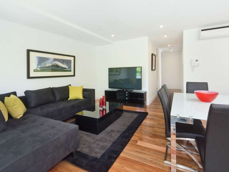 living area with Australian art and TV, floor rugs in amazing luxury short stay in Elwood Vic - 108/60-62 Broadway