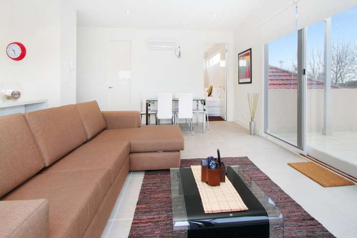 Open Plan living room with Australian art kitchen in rear and bedroom in view in luxury apartment in East St Kilda -  12/114a Westbury Close