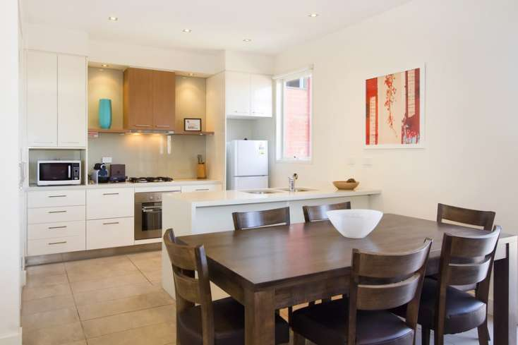 Dining area and designer kitchen in the background in a luxury apartment in East St Kilda -  13/114a Westbury Close