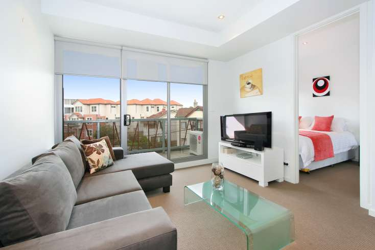 Open Plan living room with flat screen TV and Australian art leading to master bedroom in luxury 1 bedroom apartment in St Kilda - 14/23 Irwell Street