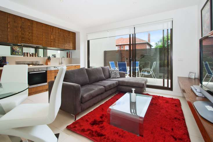 Open plan living with flat panel TV leading onto outdoor dining area in Luxury apartment in St Kilda Vic - 208/27 Herbert Street