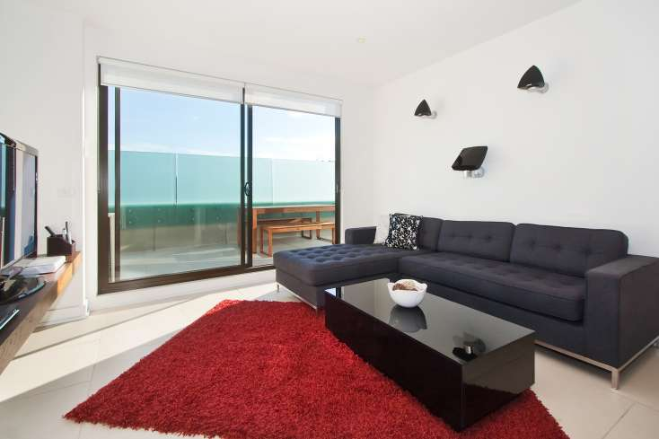 Large living area with couch and flat screen TV leading to balcony area in Luxury apartments in St Kilda - 308/27 Herbert Street