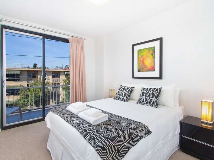 Master bedroom with wall art and view to street in short stay executive apartment in St Kilda - 32/220 Barkly Street