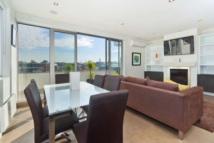 Open Plan living room with wall mounted flat screen TV and dining room  in luxury short stay in St Kilda - 32/23 Irwell Street