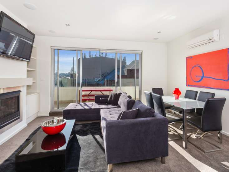 Open Plan living and dining room with flat screen TV and Australian art, leading to balcony in  luxury St Kilda apartment - 34/23 Irwell Street