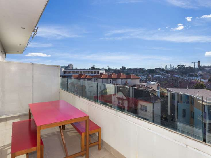 Outdoor balcony with entertaining area and timber table and chairs in luxury St Kilda apartment - 34/23 Irwell Street