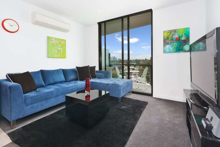 Open Plan living room with flat screen TV and Australian art, blue modular lounge in luxury executive apartment in Prahran Vic - 413/87 High Street