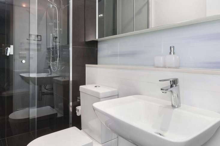 Dark grey wall tiles are an inclusion in the Luxury bathroom with glass screen shower recess and above counter hand basin in luxury St Kilda apartment - 702/181 St Kilda Road