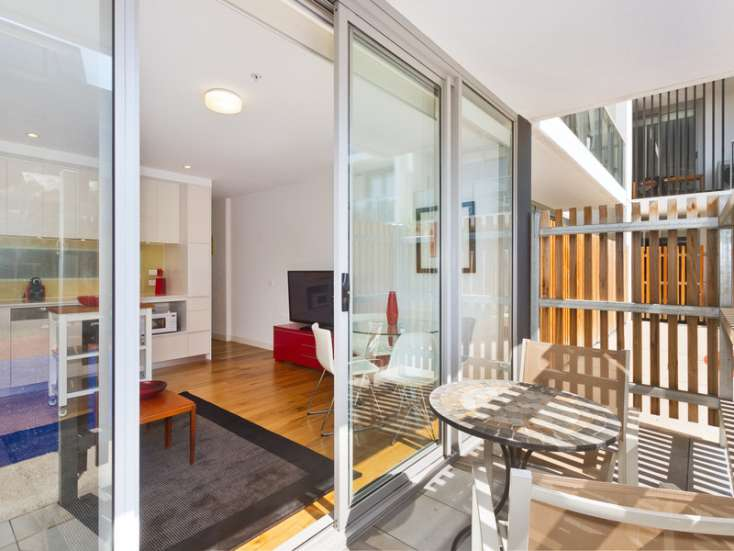 Outdoor balcony with entertaining area and table and chairs, looking into living area  in luxury Port Melbourne apartment - G10/70 Nott Street